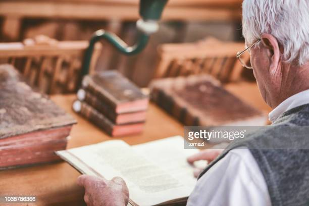senior man in library studying antique books - history stock pictures, royalty-free photos & images