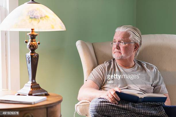 Senior man in living room reading book