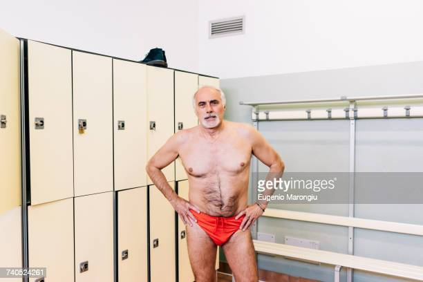senior man in locker room of swimming pool - zwembroek stockfoto's en -beelden
