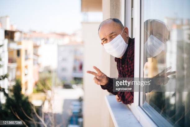 senior man in medical mask on window breathing fresh air from quarantine - turkey middle east stock pictures, royalty-free photos & images