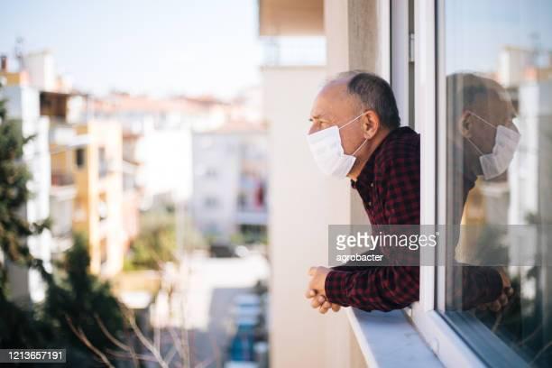senior mann in medizinischer maske auf fenster atmen frische luft aus quarantäne - quarantäne stock-fotos und bilder