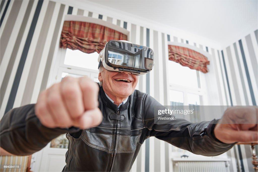 Senior man in motorcycle suit wearing VR glasses : Stock Photo