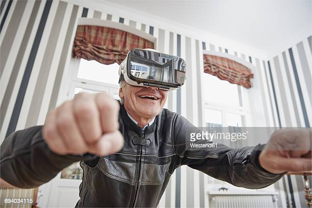 senior man in motorcycle suit wearing vr glasses - young at heart stock pictures, royalty-free photos & images