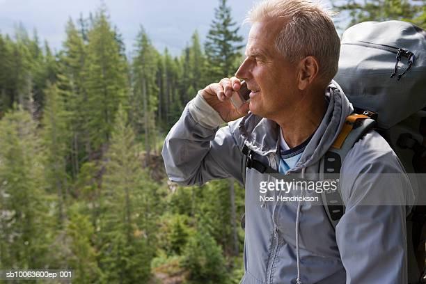 senior man in mountains talking on mobile phone, smiling - einzelner senior stock-fotos und bilder