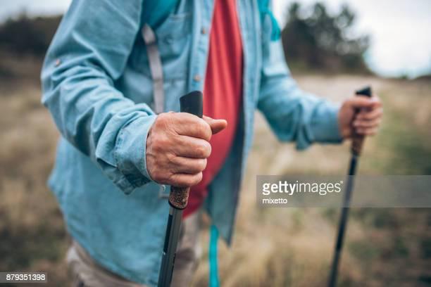 Senior man in nature walk using sticks for hiking