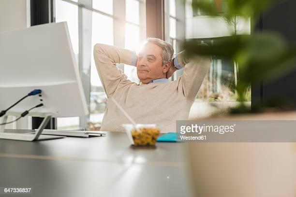 senior man in office, during break - zurücklehnen stock-fotos und bilder