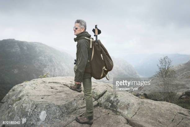 Senior man in old school clothes trekking in mountains in Norway