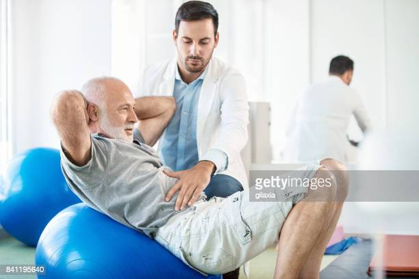 senior man in physical rehab. - back pain stock pictures, royalty-free photos & images