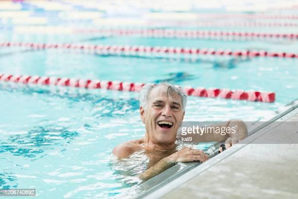 水泳ラップから休憩を取るプールのシニア男性 - スポーツ用語 ラップ ストックフォトと画像