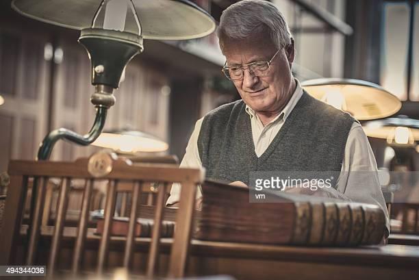 Senior hombre en biblioteca pública