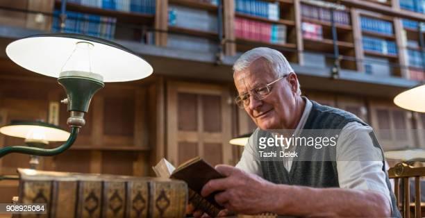 senior woman in public library - einzelner senior stock-fotos und bilder