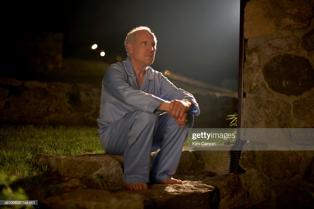 Senior man in pyjamas sitting outside house at night : Stock Photo