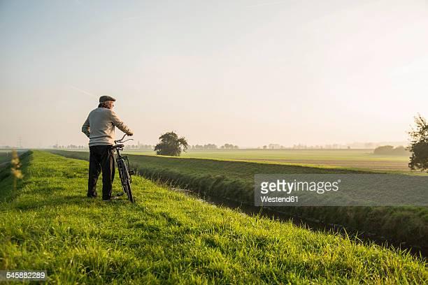 Senior man in rural landscape pushing bicycle