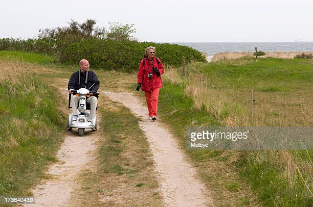 senior man in scooter and woman walking on nature path - mobility scooter stock photos and pictures