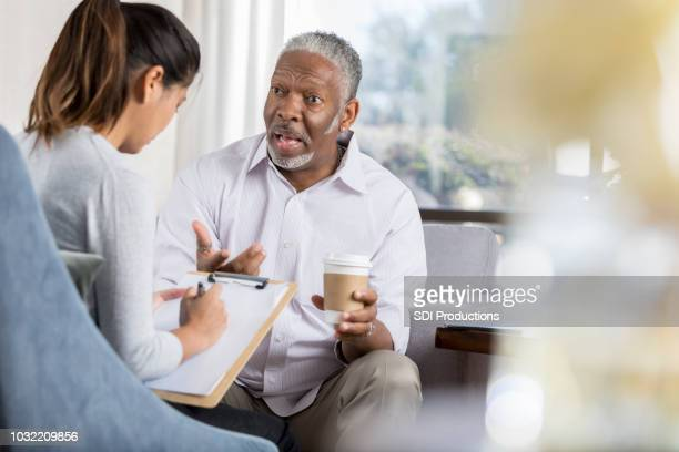 senior man in serious conversation with therapist - vulnerability stock pictures, royalty-free photos & images