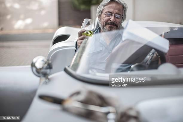 Senior man in sports car looking at check list drinking lemonade
