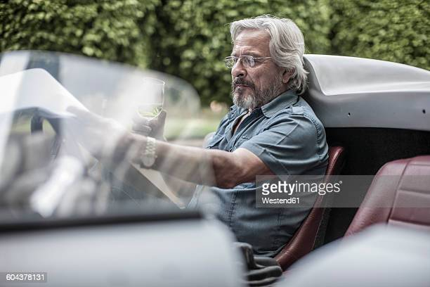 Senior man in sports car looking at check list drinking lemonade