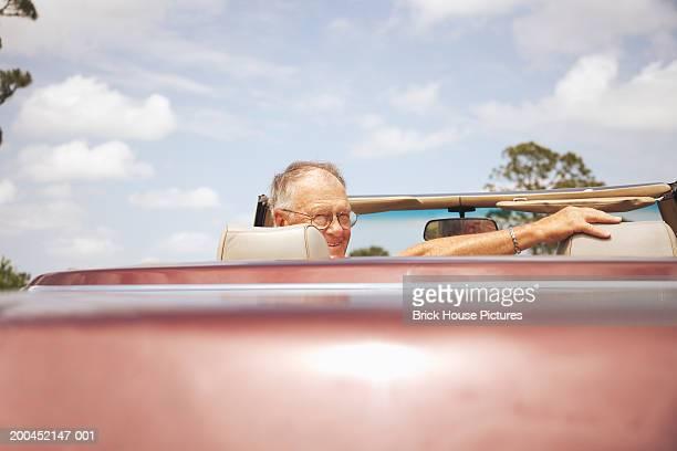 senior man in sports car, looking over shoulder - terugtrekken stockfoto's en -beelden