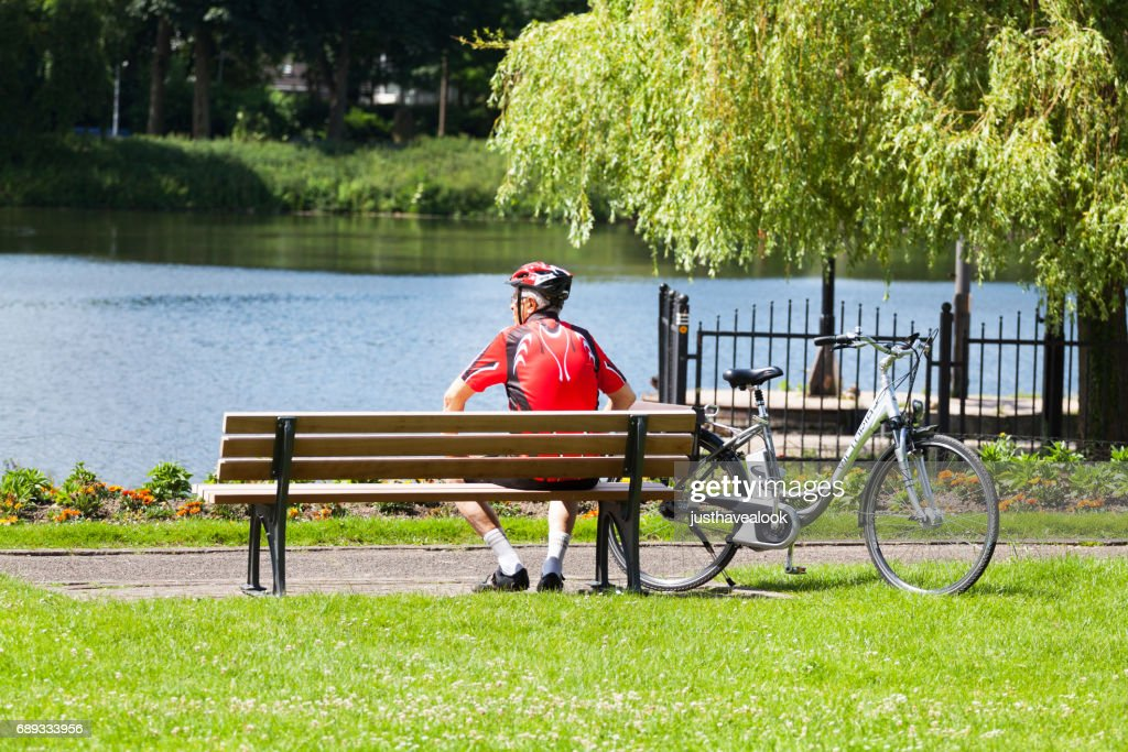 Senior man in sports dress relaxing on bench at Ruhr : Stock Photo
