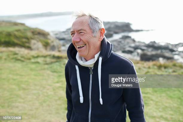 senior man in sportswear laughing on rocky coastline. - dougal waters stock pictures, royalty-free photos & images