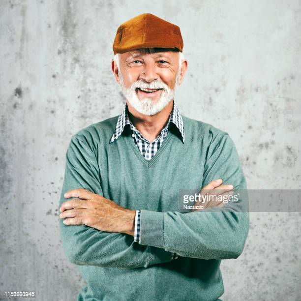 senior man in sweater and beret posing - flat cap stock pictures, royalty-free photos & images