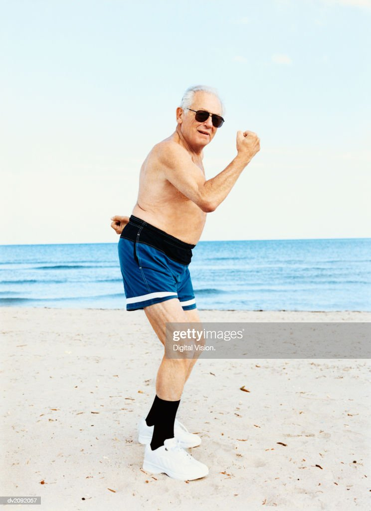Senior Man in Swimming Trunks Stands on the Beach Flexing His Muscles : Stock Photo