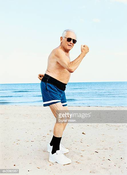 senior man in swimming trunks stands on the beach flexing his muscles - zwembroek stockfoto's en -beelden