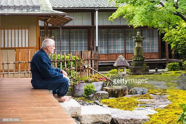 senior man in temple garden - karesansui photos et images de collection