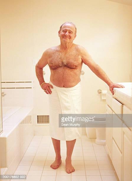 Senior man in towel, standing in bathroom, portrait