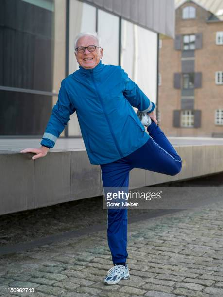 senior man in tracksuit doing warmup exercises on cobbled street, portrait, copenhagen, hovedstaden, denmark - standing on one leg stock pictures, royalty-free photos & images