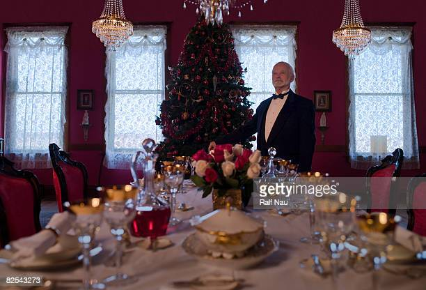 Senior man in tuxedo standing at head of table