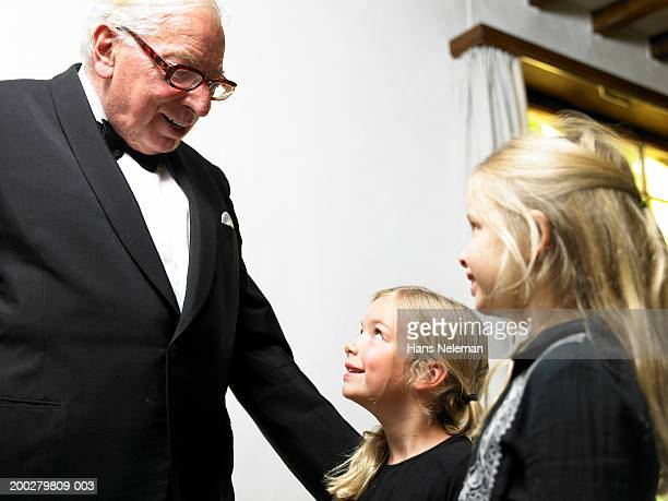 Senior man in tuxedo talking with girls (5-7), smiling, side view