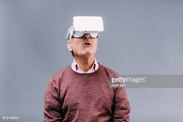 senior man in virtual reality experience - head mounted display stock photos and pictures