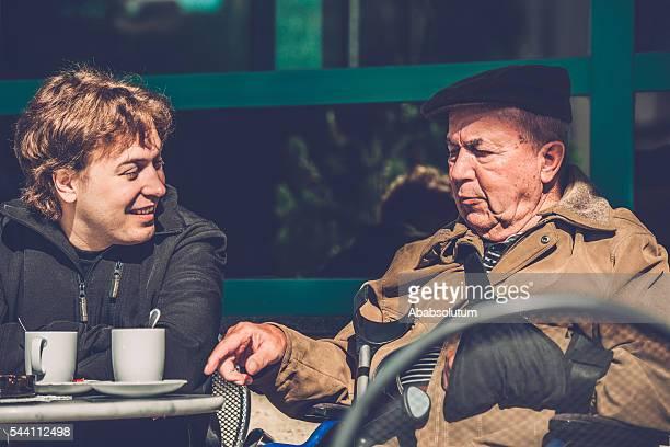Senior Man in Wheelchair and Grandson Having Coffee, Europe