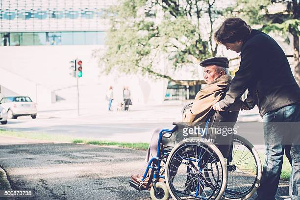 Senior Man in Wheelchair and Grandson in the City, Europe