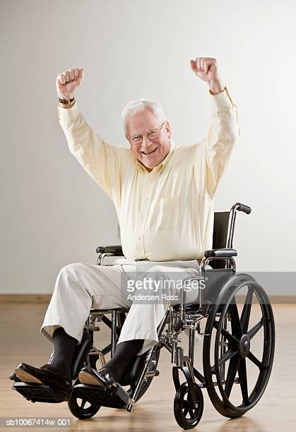 Senior man in wheelchair laughing with arms outstretched, portrait
