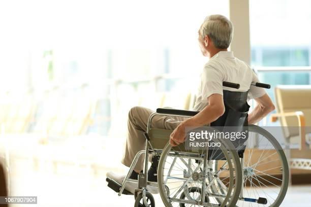 senior man in wheelchair looking out window - begeleid wonen stockfoto's en -beelden