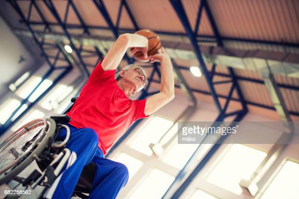 Senior man in wheelchair playing basketball