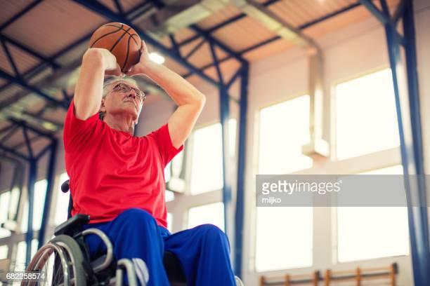 hombre mayor en silla de ruedas jugando baloncesto - taking a shot sport fotografías e imágenes de stock