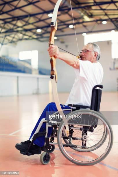 車椅子アーチェリーの練習で年配の男性 - 麻痺 ストックフォトと画像