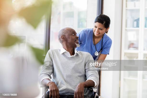 senior man in wheelchair receives medical help for injury - wheelchair stock pictures, royalty-free photos & images