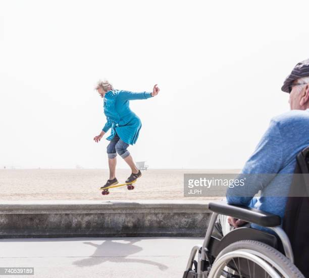 Senior man in wheelchair watching wife doing skateboard trick at beach, Santa Monica, California, USA