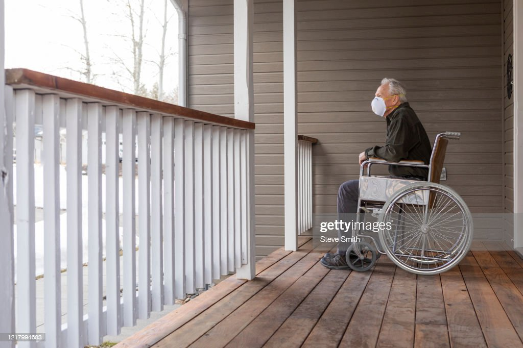 Senior man in wheelchair wearing protective mask to prevent coronavirus transmission on porch : Stock Photo