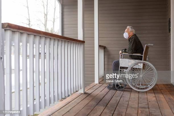 senior man in wheelchair wearing protective mask to prevent coronavirus transmission on porch - altersheim stock-fotos und bilder