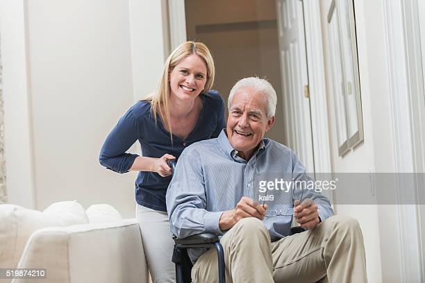 Senior man in wheelchair with caregiver at home