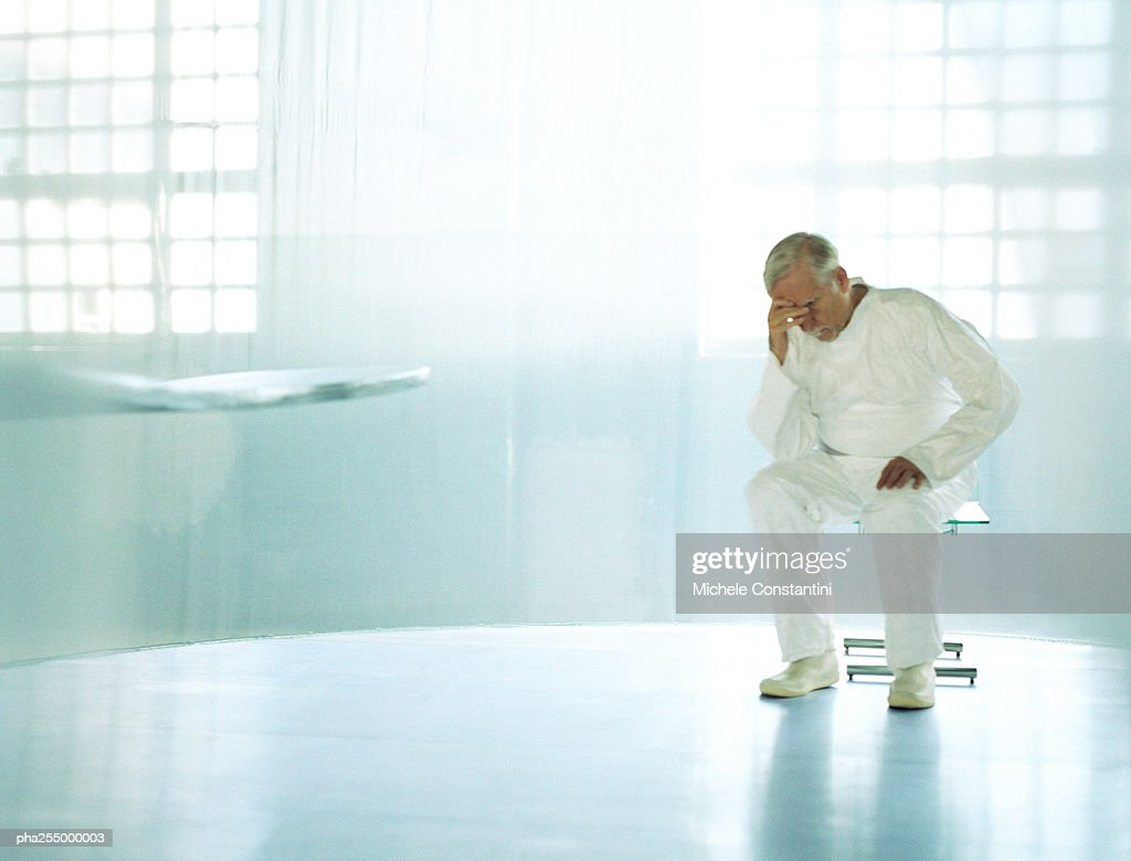 Senior man in white sitting in spacious room, head on hand : Stock Photo