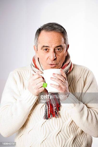 Senior man in winter clothes drinking cup of tea