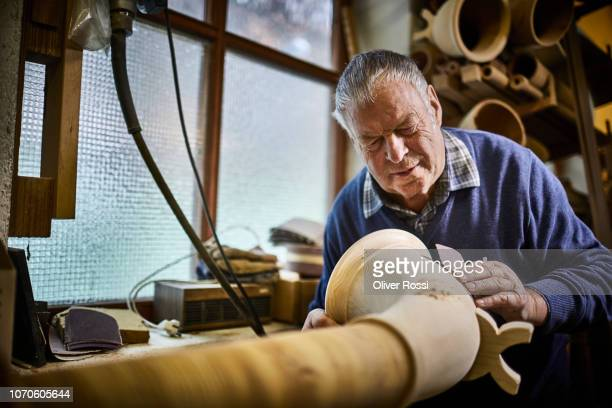 Senior man in workshop making alpenhorn using sand paper