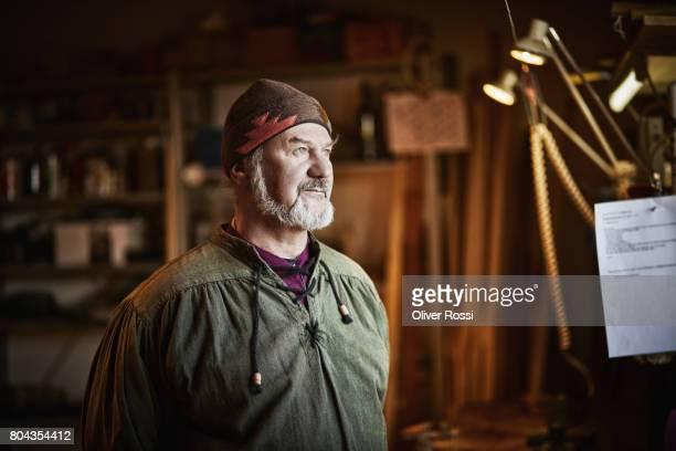 senior man in workshop thinking - handwerker stock-fotos und bilder