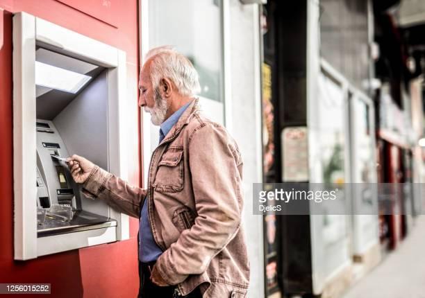 senior mann einstecken eine kreditkarte in geldautomaten. - geldautomat stock-fotos und bilder